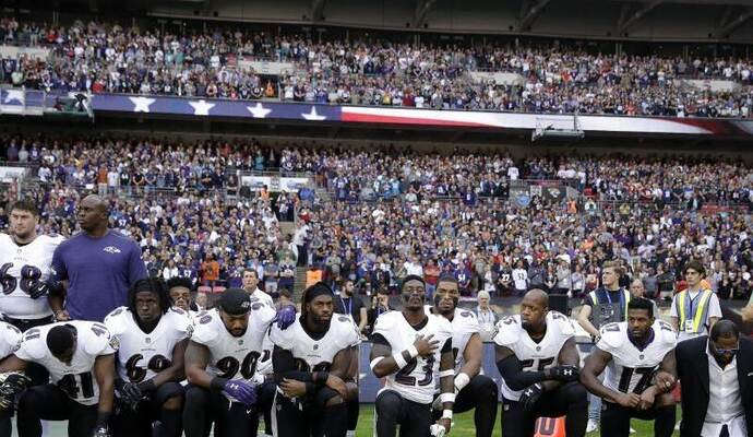 Spieler des Football-Teams Baltimore Ravens knien in London während der US-Nationalhymne aus Protest auf dem Rasen. Foto